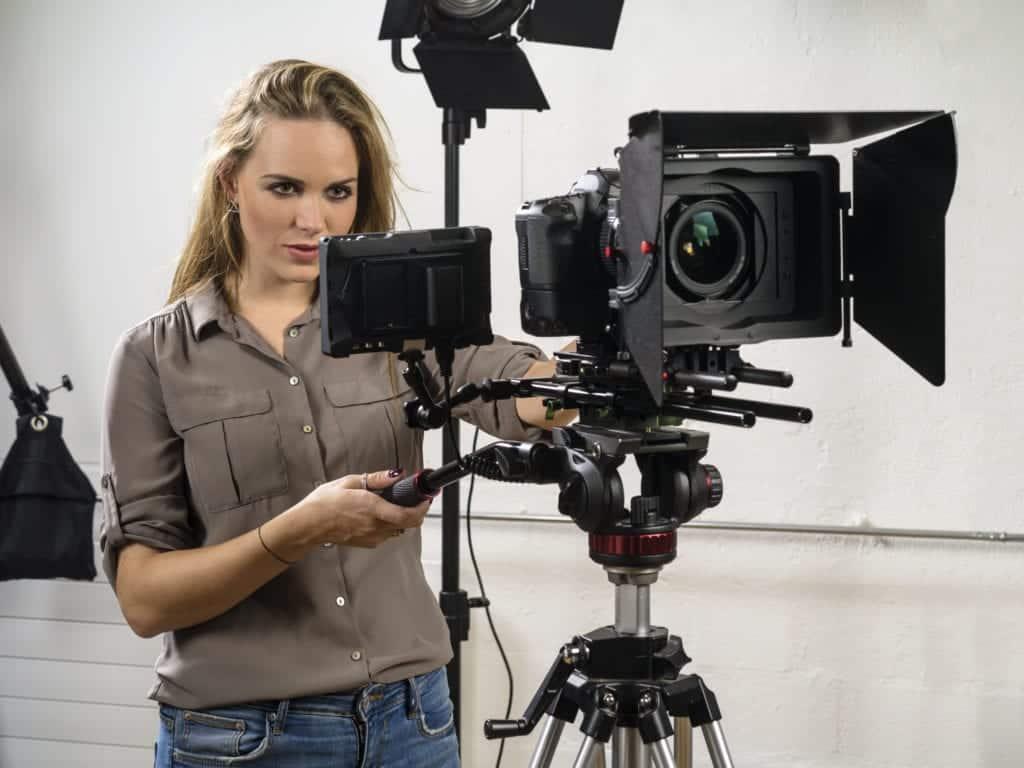 beautiful woman operating a video camera rig KLM9QZV