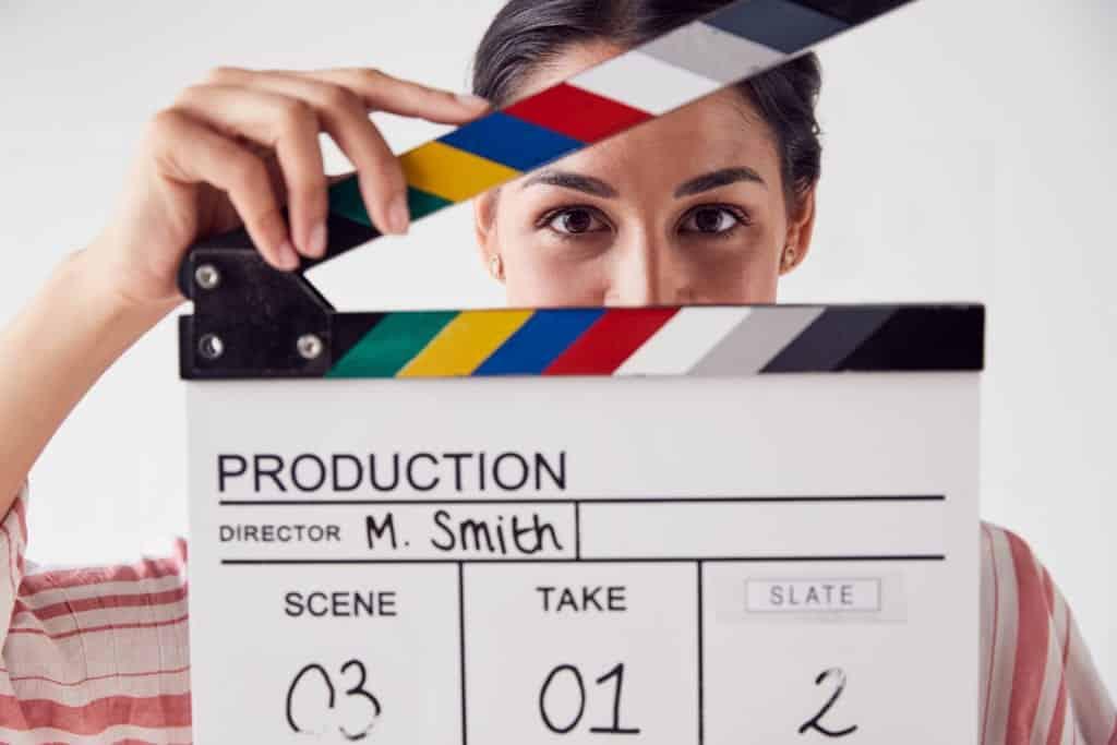 portrait of female videographer holding clapper bo DGXRCJY